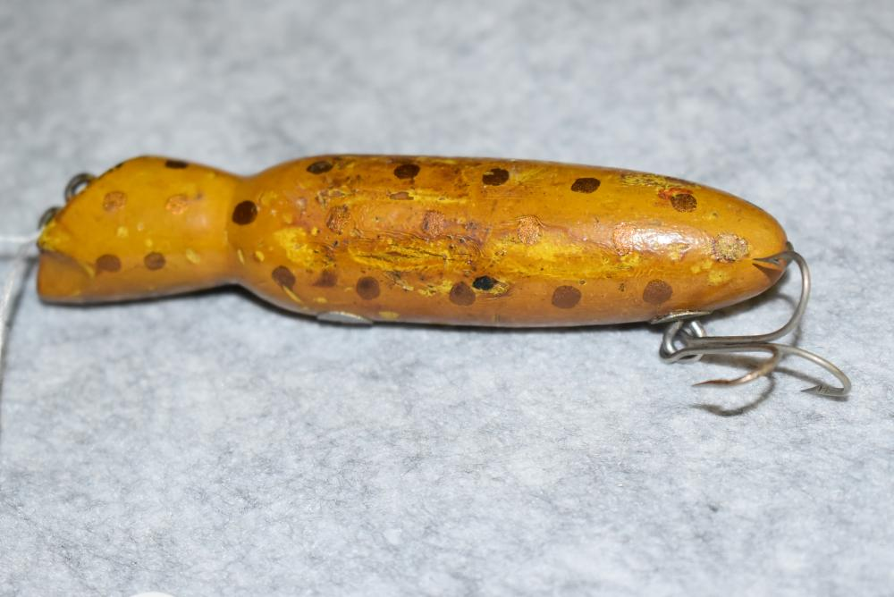 """Miller's Prototype Lure – Measures 4¼"""" in Length – Round Body w/Slant Face w/ Double Line Tie – Has 1 Belly Hook Remaining – Screw Eye & Washer Hardware – Tail Nail – Yellow w/Gold Spots – Some Finish Blemishes"""