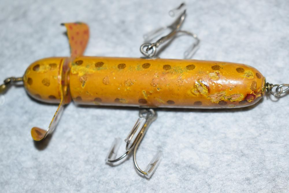 """Miller's Rotary Head Prototype Minnow – Measures 4"""" in Length – Has Single Blade Which is Painted w/Gold & Red Spots – Has Wire Through Body – 2 Side Hooks w/Screw Eye & Washer Hardware – Yellow w/Gold Spot Finish – Dents & Blemishes to the Paint"""
