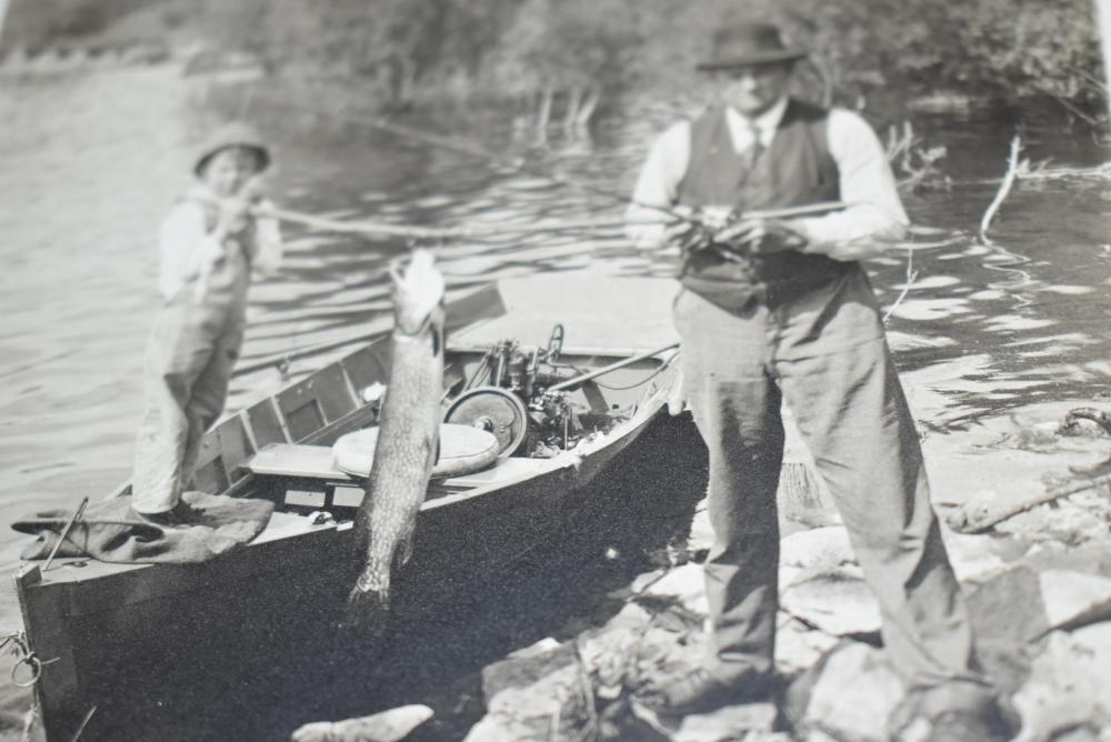 """William & Paul Miller Real Mounted Photo – Shows William H. Miller on the Bank w/ His Son Paul Standing in the Boat Helping to Hold Up a Large Northern Pike – The Lure on the End of William's Line Looks Like His Miller's Reversible Minnow – Image Measures 7½"""" x 9½"""" Matted – Signed on back: Miller's Collection By: Ed Salensky"""