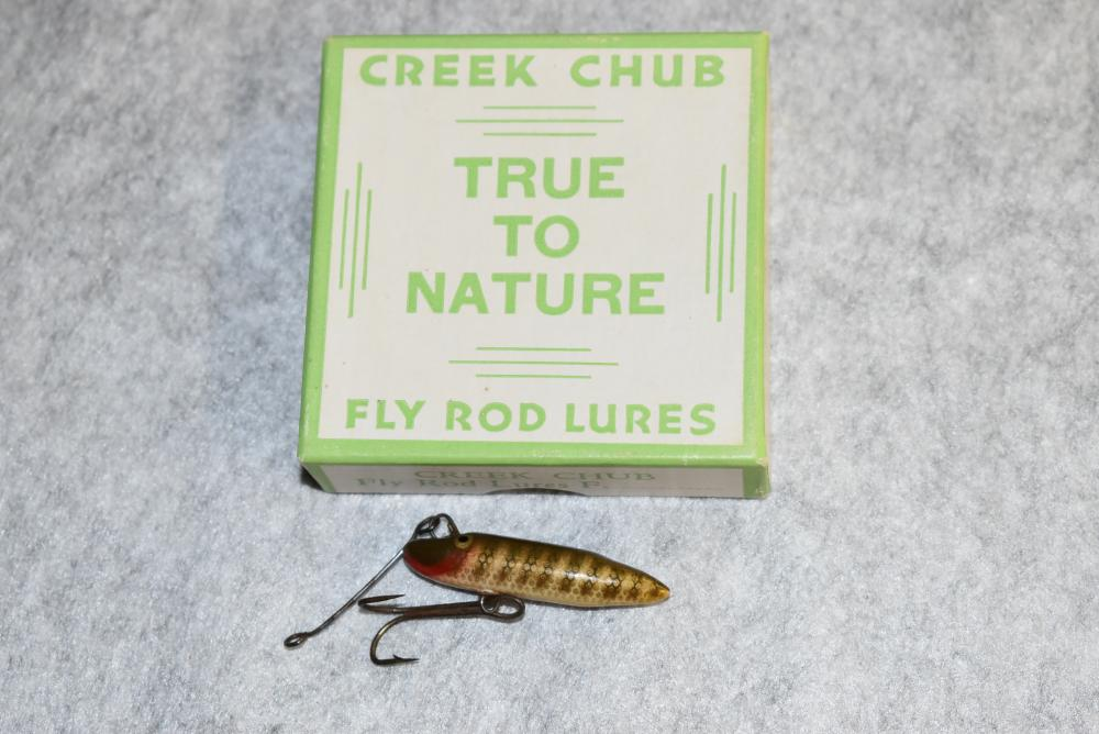 Creek Chub Bait Co. – True To Nature Fly Rod Pikie Minnow in Unmarked Box – Lure is in Pike Finish – P.E., Belly Double Hook – Wire Line Tie – Hook Pointer in Front of the Right Eye – Age Crack on Belly – Box Has Strong Colors & All Corners Intact (VG+)