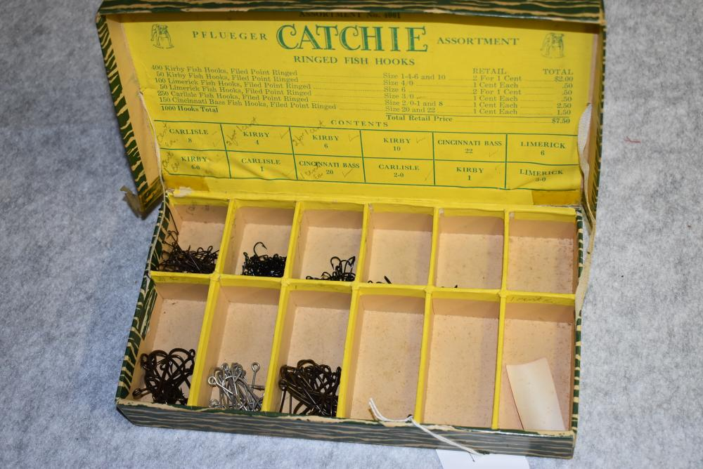 Pflueger Catchie Assortment. Ringed fish hooks No. 4001. Has a hinged lid, label inside of lid. Has tape repair on hinge, few hooks remain.
