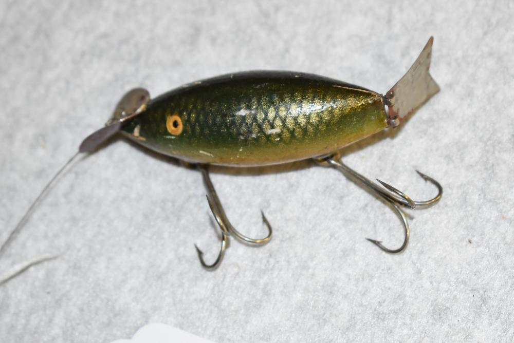 Lane's Wagtail wobbler. Pat. Date of 3-16-20. Has tiny glass eyes, cup rig hardware, has the articulated tail, green scale finish. Wire line tie, signed on the lip: Chas. W. Lane, PTD.3-16-20 Madrid NY, has a few scuffs and dents, a small chip around the lip (VG)