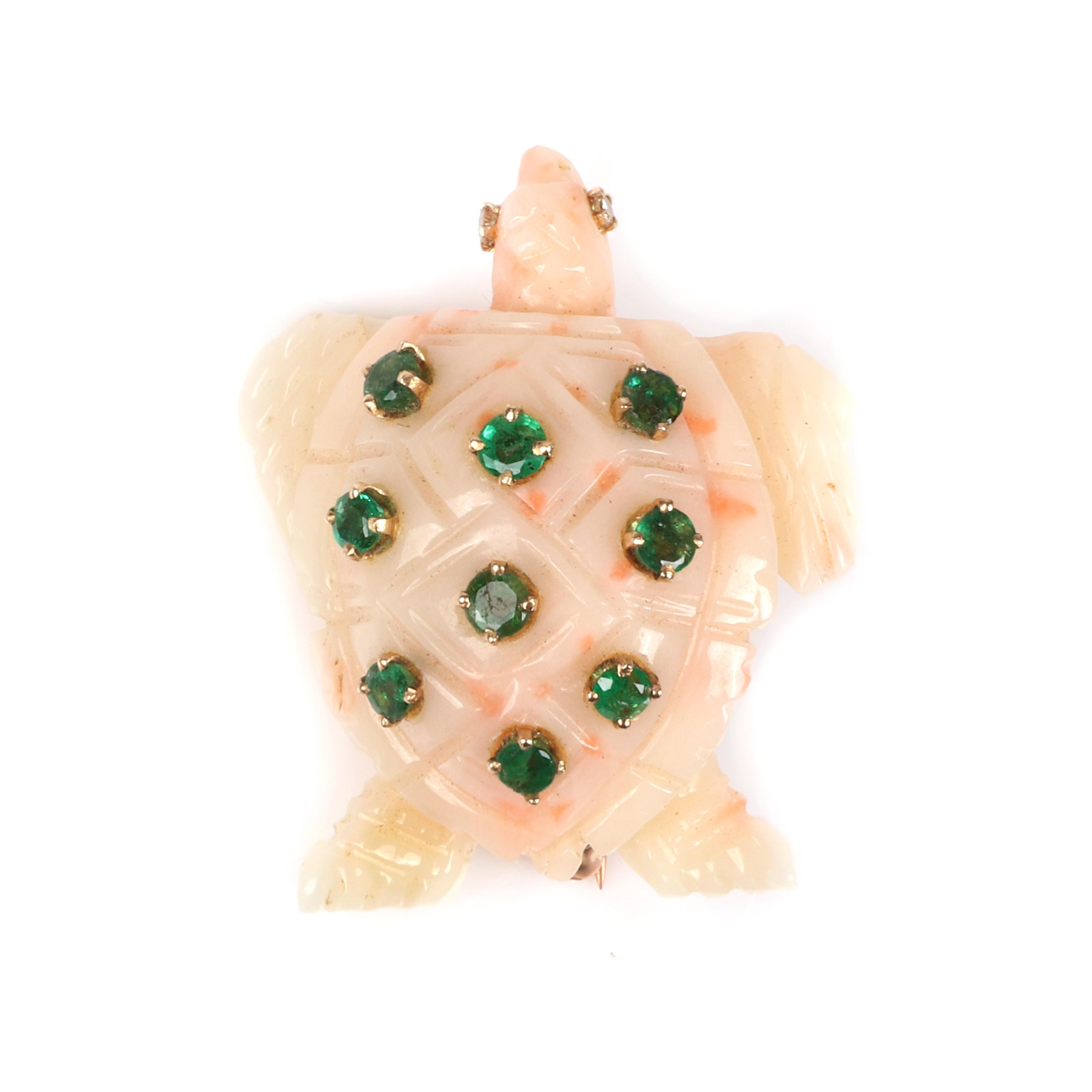 """Stamped 18K yellow gold and carved pink, angel skin coral figural turtle pin brooch with round diamond eyes, and nine round emerald accents. 1 3/8""""H x 1 1/4""""W. 8.30 dwt."""
