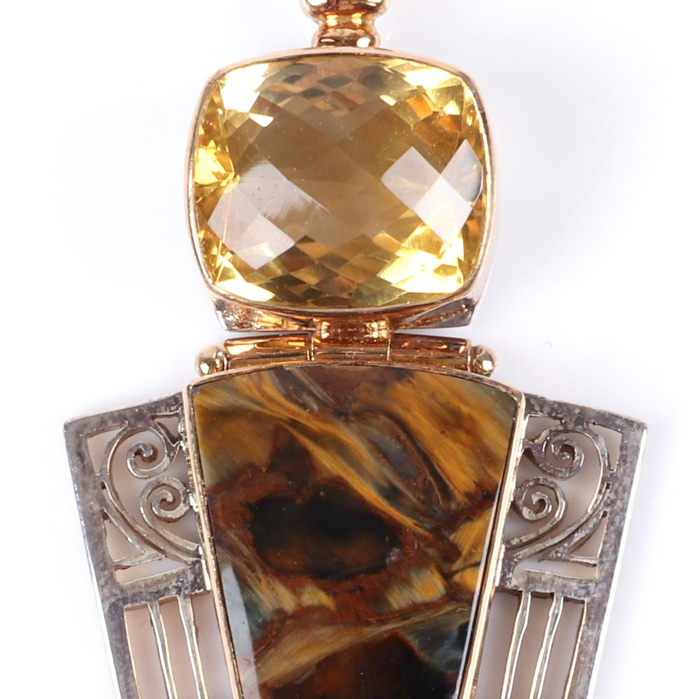 """Hinged artisan designer pendant stamped 18K white & yellow gold with bezel set cushion cut citrine, packsaddle tiger eye, and black onyx cabochon with fine open metalwork detail in white gold. 2 3/4""""H x 1 3/4""""W"""