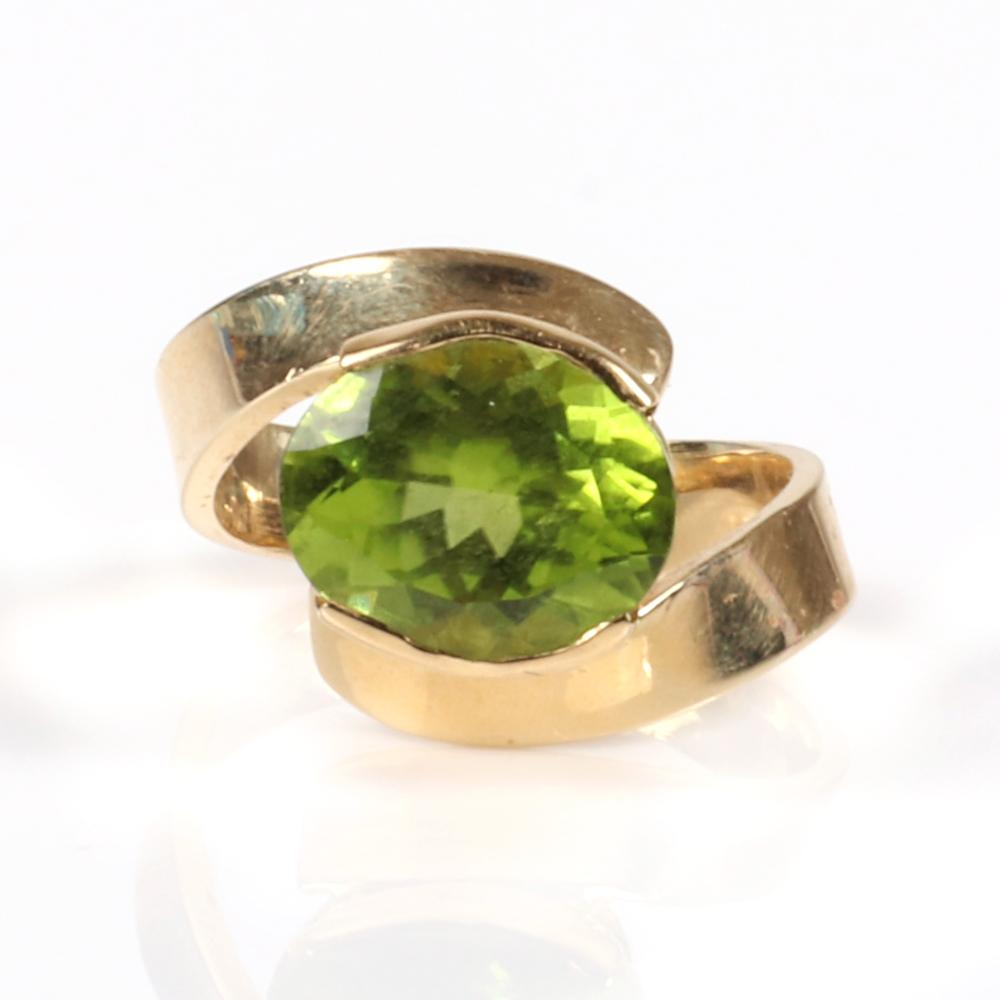 Stamped 14K yellow gold oval peridot ring with bypass design. Ring Size 6