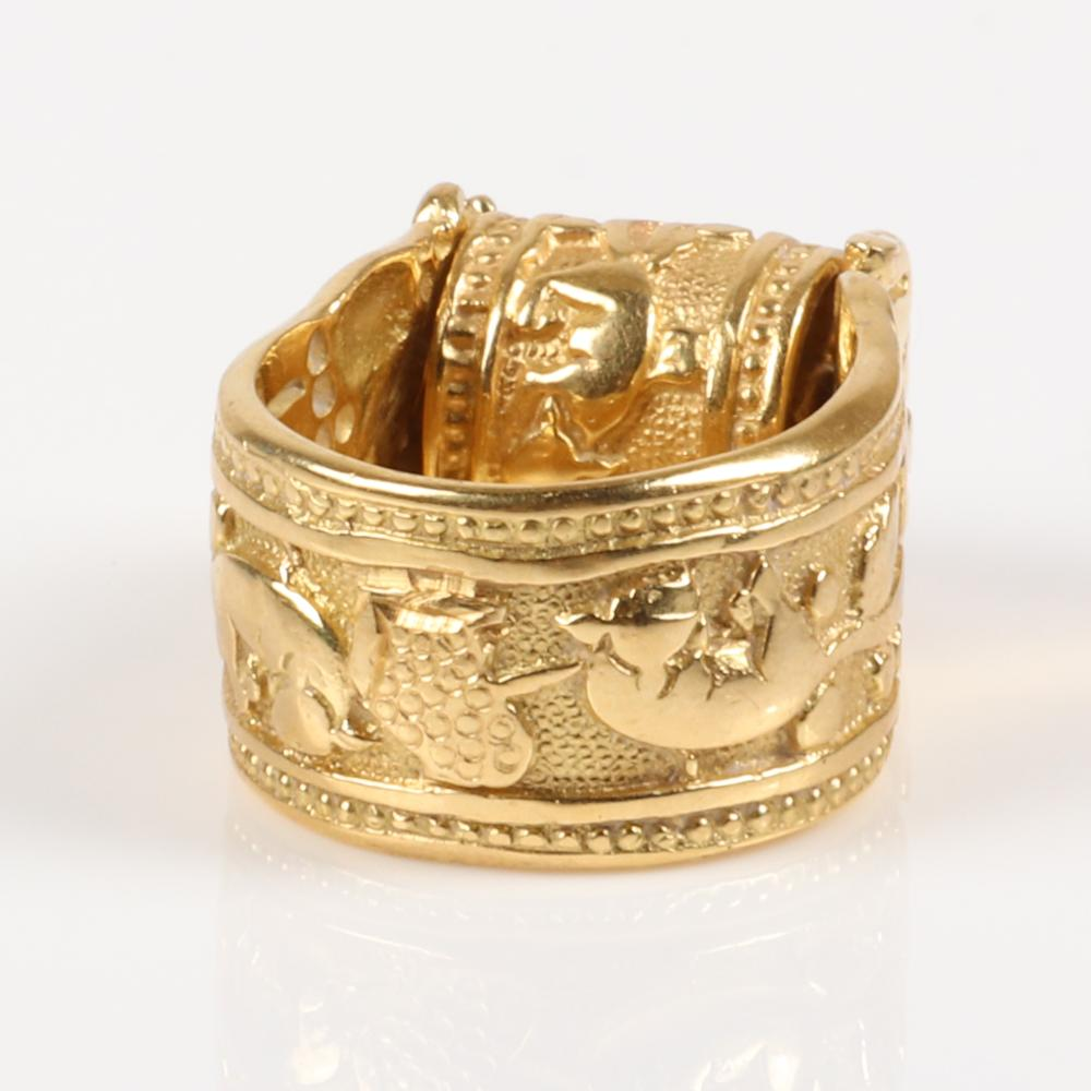 Egyptian Revival Stamped 18K gold zodiac barrel spinner ring, Minotaur or Taurus the bull, with stippled and polished relief decoration on wide band, 13.50 dwt. Ring Size 6 1/2