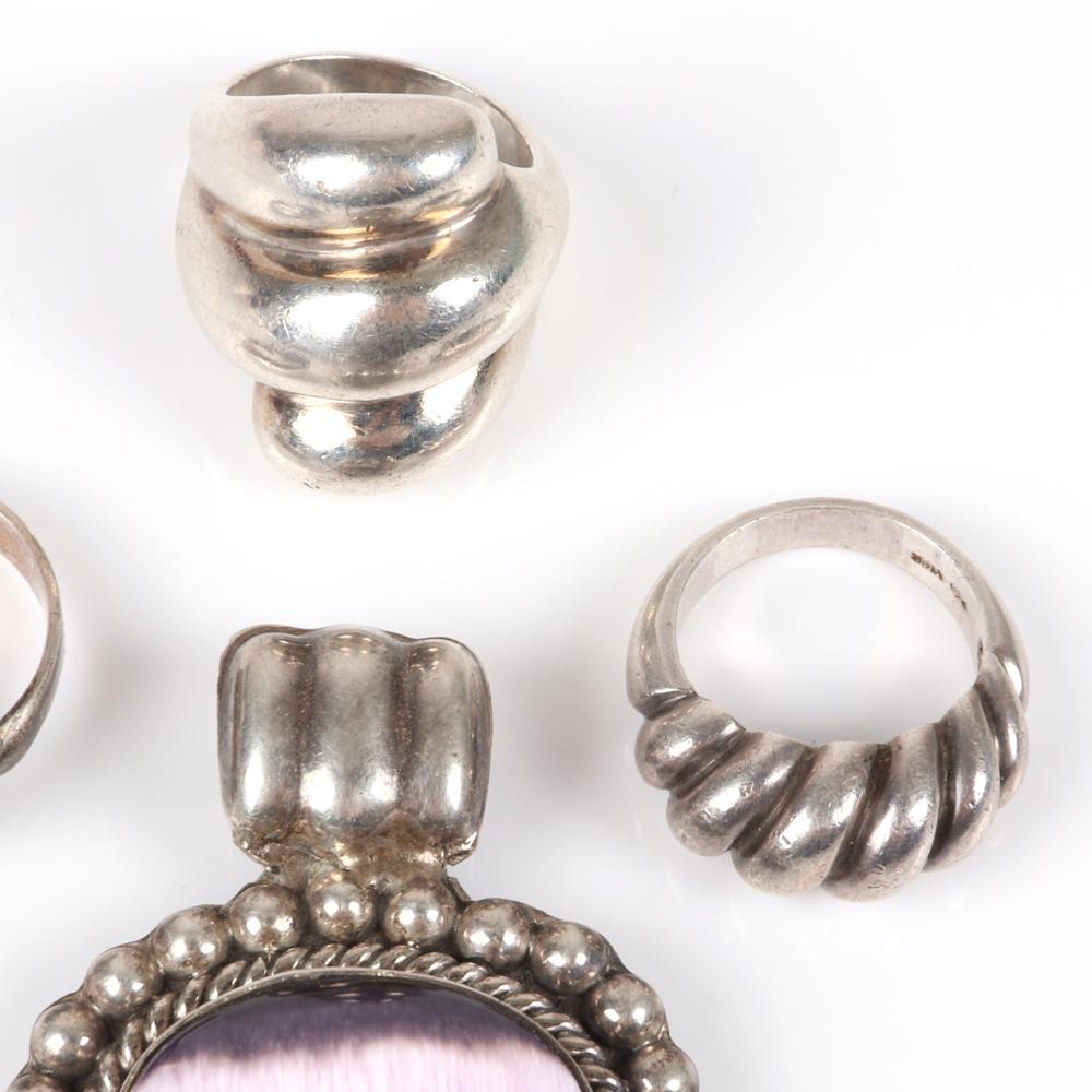 """Sterling silver 4pc marked group: large 1950s Mexican silver pendant with lavender cabochon, three signed designer twist rings. RIng Size 5 3/4, 2""""H (pendant)"""