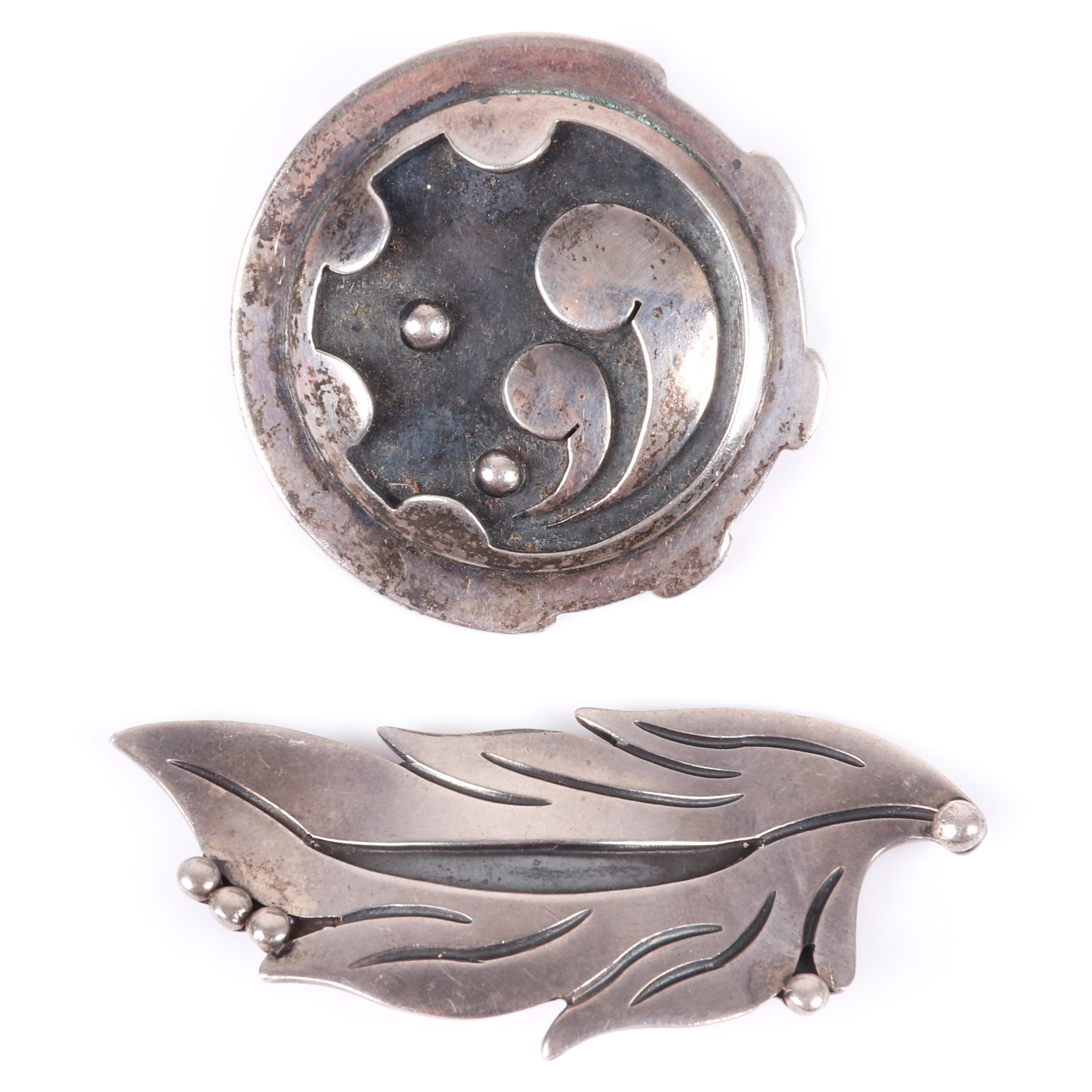 """Two Mexican Modernist sterling silver pins: Maricella Taxco carved leaf form brooch and round layered pin with wave forms in relief. 2 1/8""""H (leaf)"""