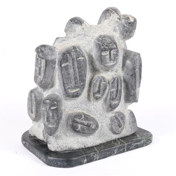 Charles (C.R.) Schiefer, (Indiana, 1925-2018), many faces / Inuit masks, ca.1985, LARGE carved soapstone sculpture on marble plinth,...