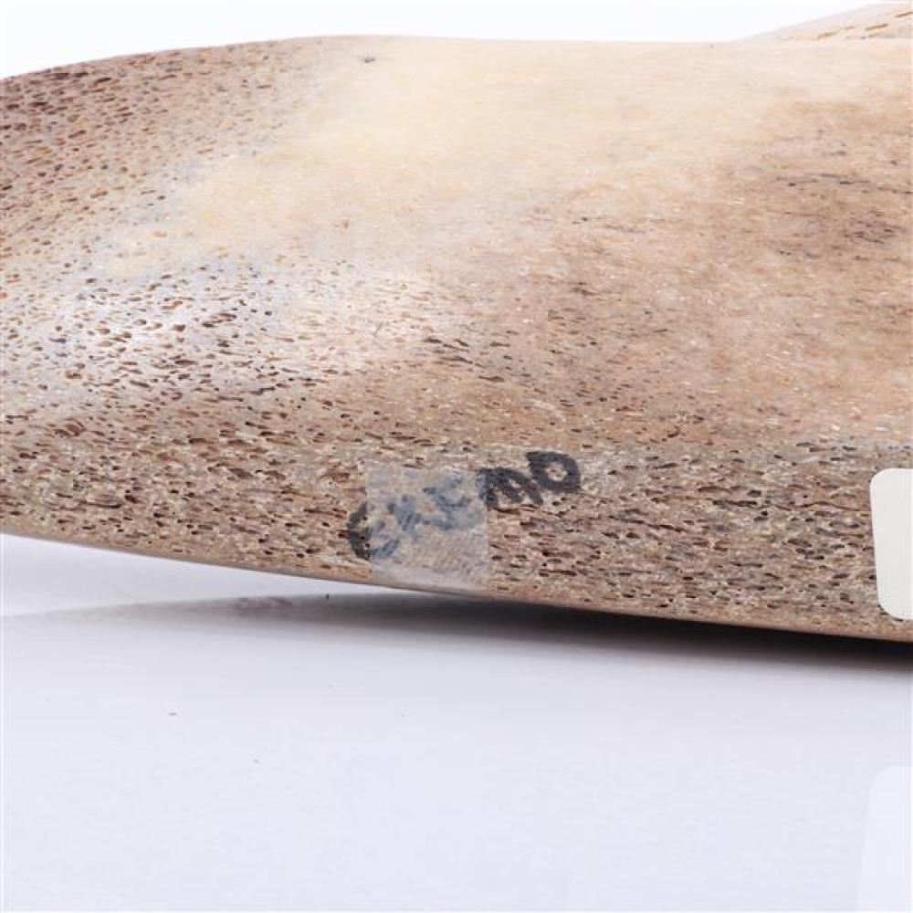 Alaskan Eskimo / Inuit seal hunter in kayak folk art carving of fossil whalebone signed Ekemo under base.