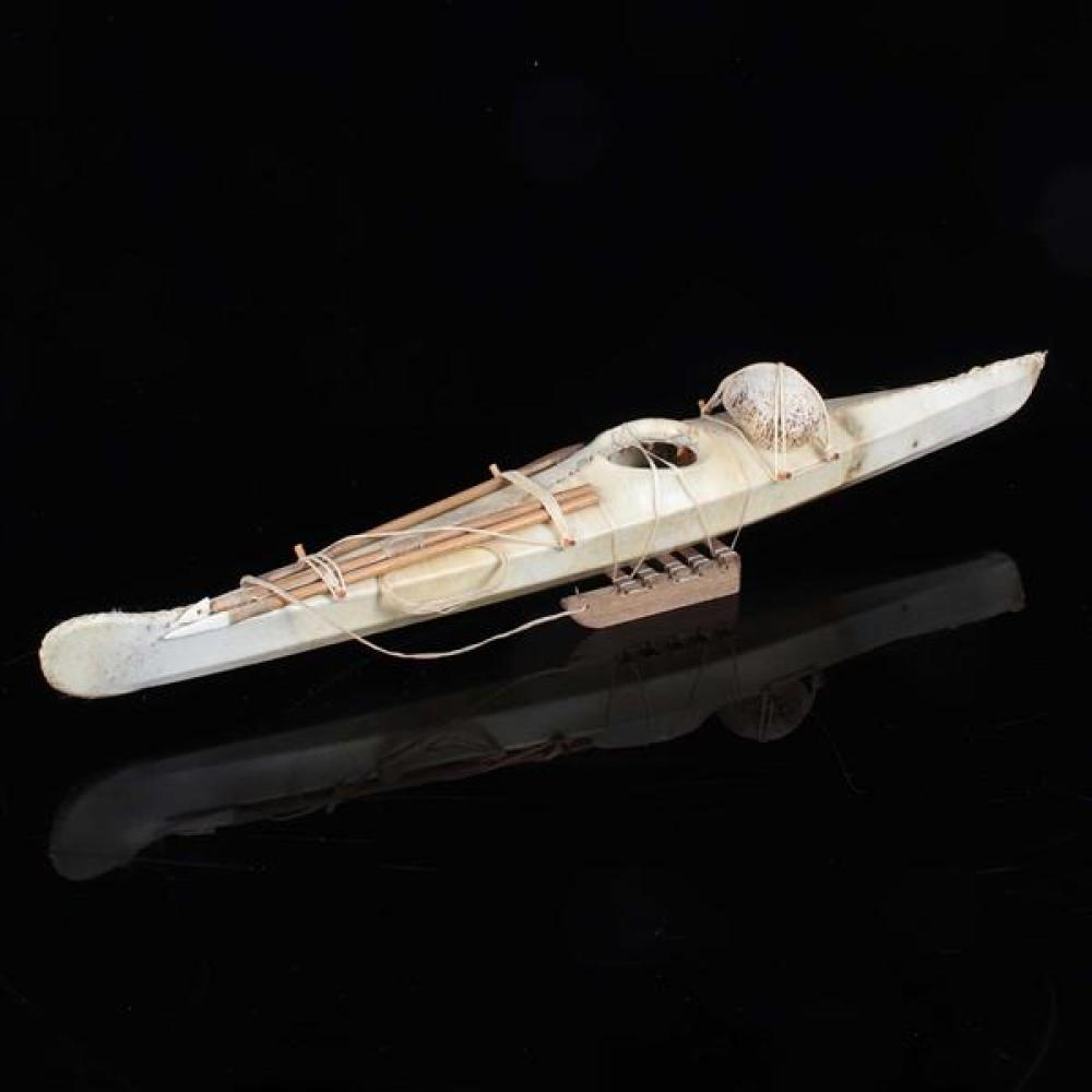 An Eskimo / Inuit seal skin and cedar wood model of a kayak with hunting gear.