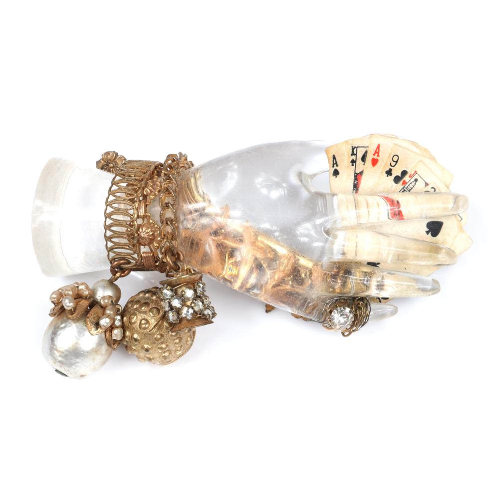 "Miriam Haskell figural lucite jelly belly hand holding six miniature playing cards and wearing a brass bracelet and ring with faux pearls and rhinestones. 1 3/4""H x 3 1/4""W"
