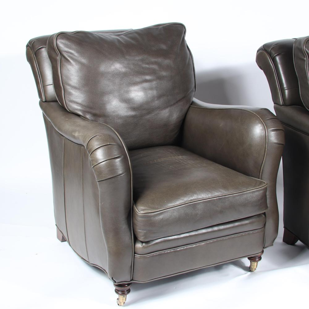 """Pair Connoisseur 'Lowell' club lounge chairs and one ottoman with olive green leather upholstery. Seat width; 19"""" x seat depth; 21 3/4"""" x seat height; 20""""."""