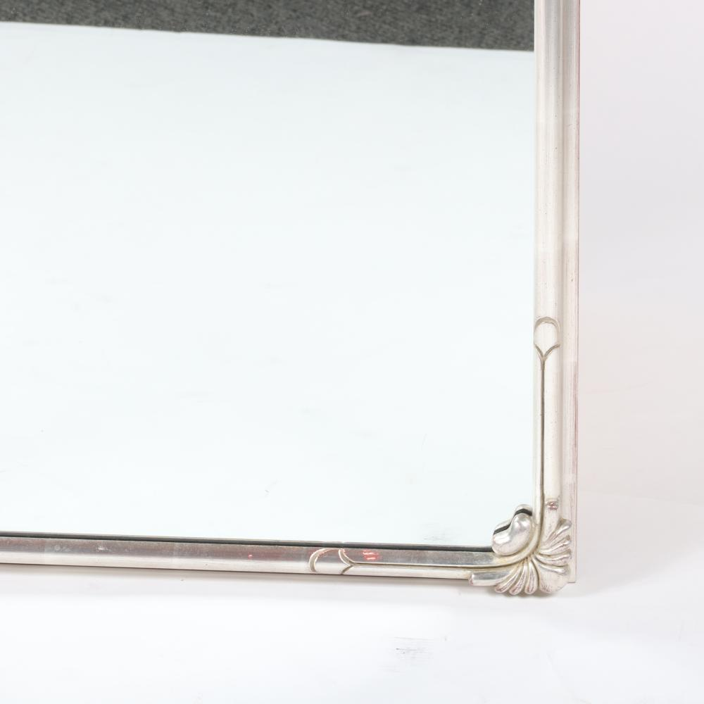 """French Art Deco style silver gilt and carved frame wall mirror with stylized floral spray motif at corners. 48""""H x 21""""W."""