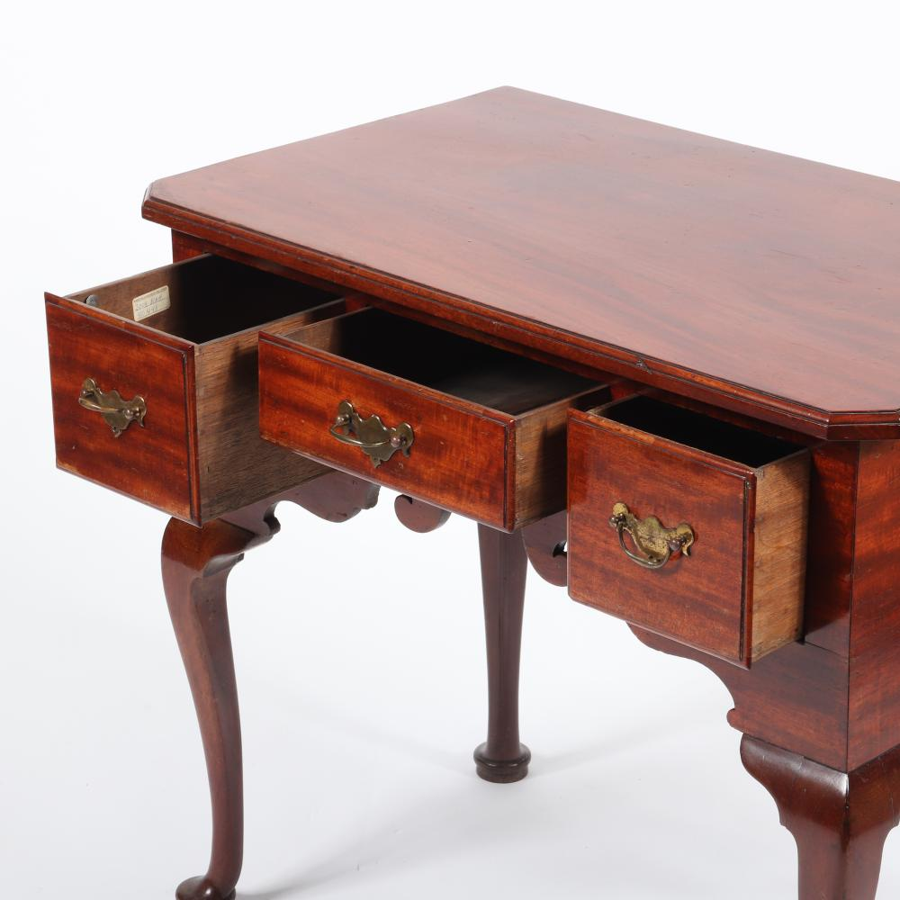 """English Georgian period lowboy; mahogany with three drawers, a scrolled apron, and four cabriole legs terminating in pad feet, c.1840. 28""""H x 31 3/4""""W x 18 3/4""""D."""