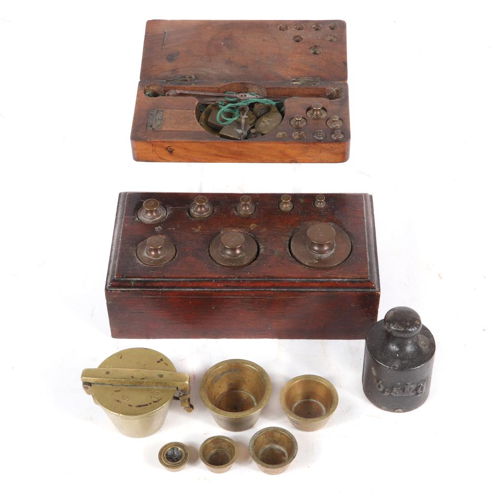"Antique counter balance weights; two sets in wooden box, one with small scale, French brass nesting set, and one 0.5kg weight. 3""H x 3 3/4""W x 7""D"