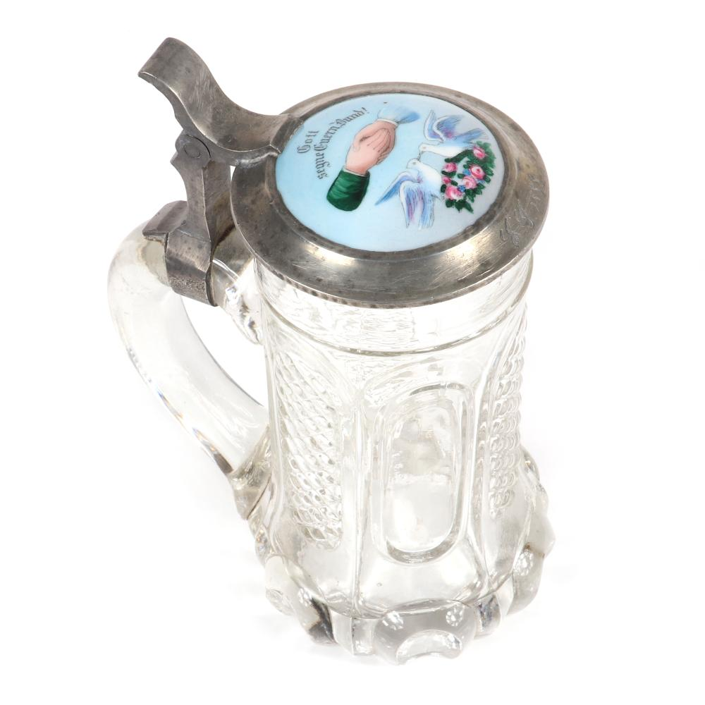 """German crystal stein with porcelain wedding plaque on pewter lid dated 1888, hand painted imagery including clasped hands, doves, and flower crown. 7""""H x 6""""W"""