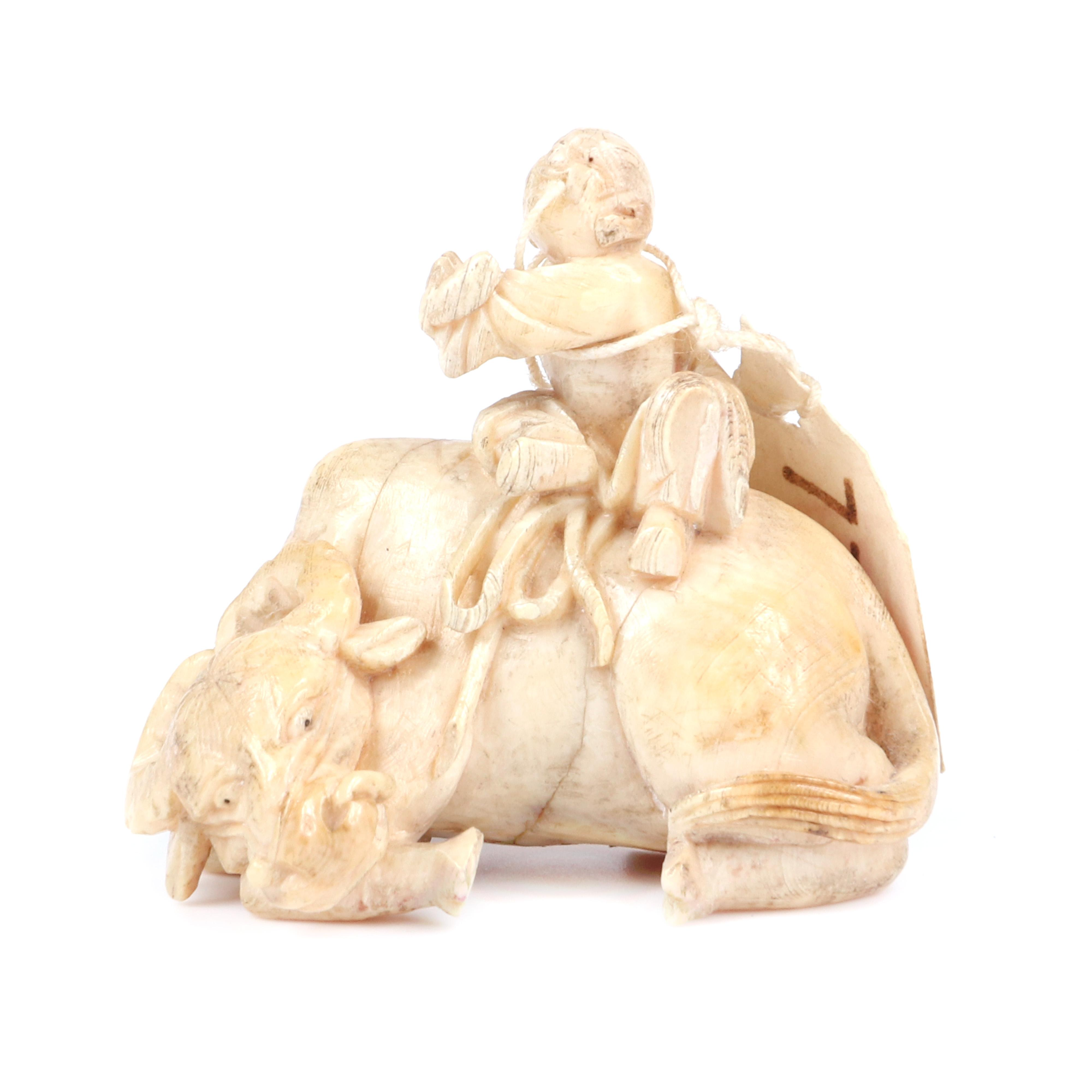 "Japanese miniature figure group carving / netsuke depicting a boy on recumbent water buffalo. Signed under base. 1 1/4""H x 1 1/2""W"