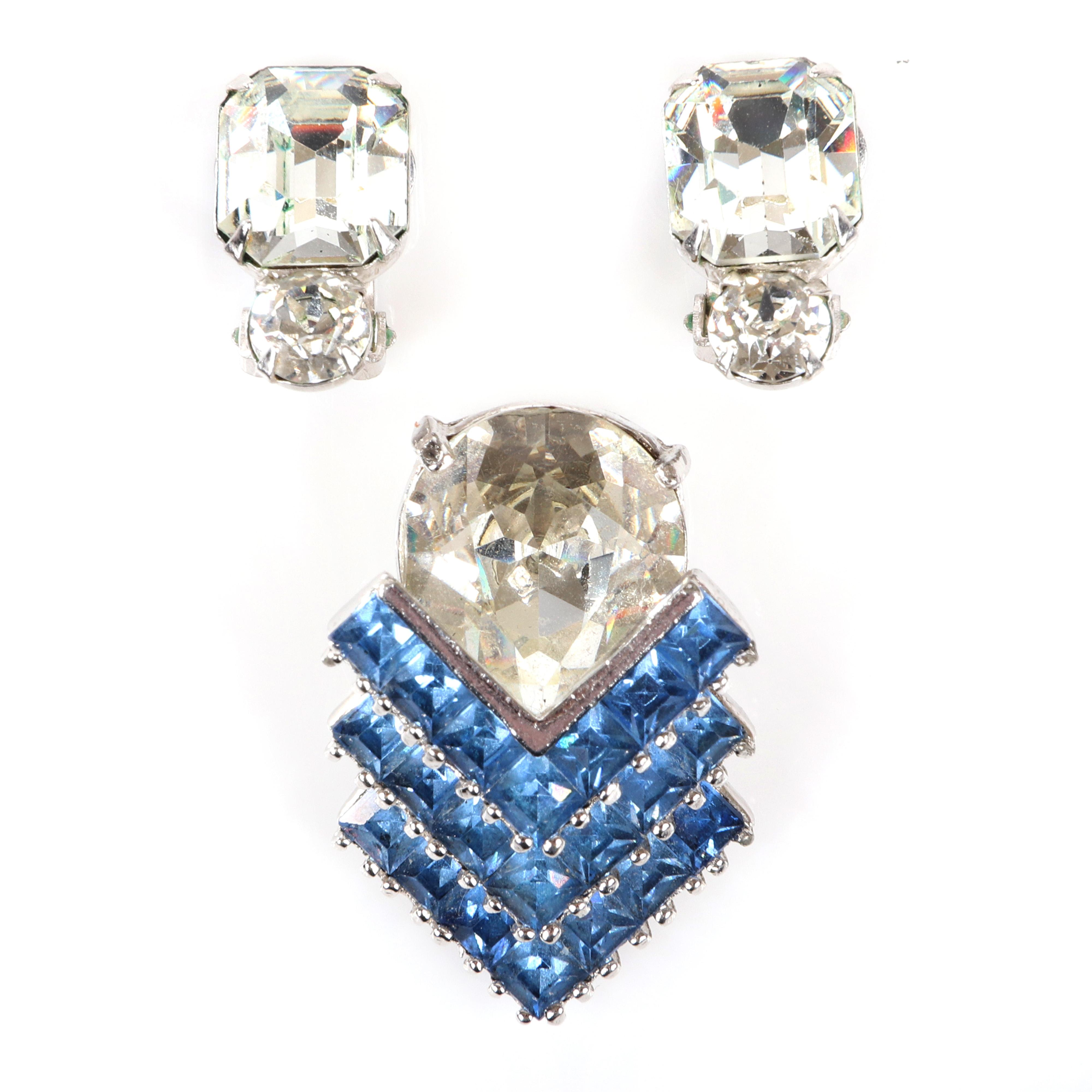"""Eisenberg blue and white dress clip with large clear faceted rhinestone and Vs of square sapphire stones, 1940s, marked script E with petite clear rhinestone earrings, c. 1950. 2 1/2"""" x 1 3/4"""" (brooch), 3/4"""" x 1/2"""""""