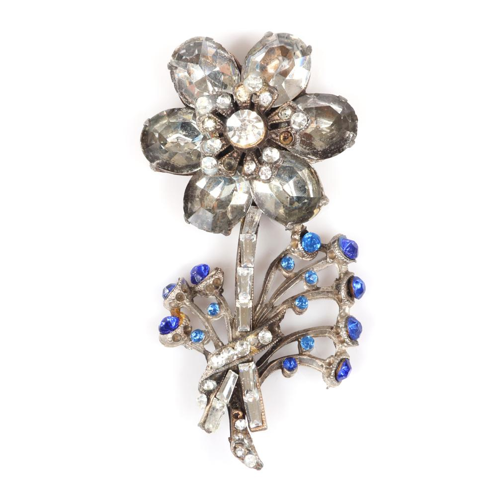 """Eisenberg Original early floral sew-on in pot metal attached by rear loops with dimensional rhinestone flower and small sprays tipped with blue rhinestones, c. 1930. 2 3/4"""" x 1 1/4"""""""