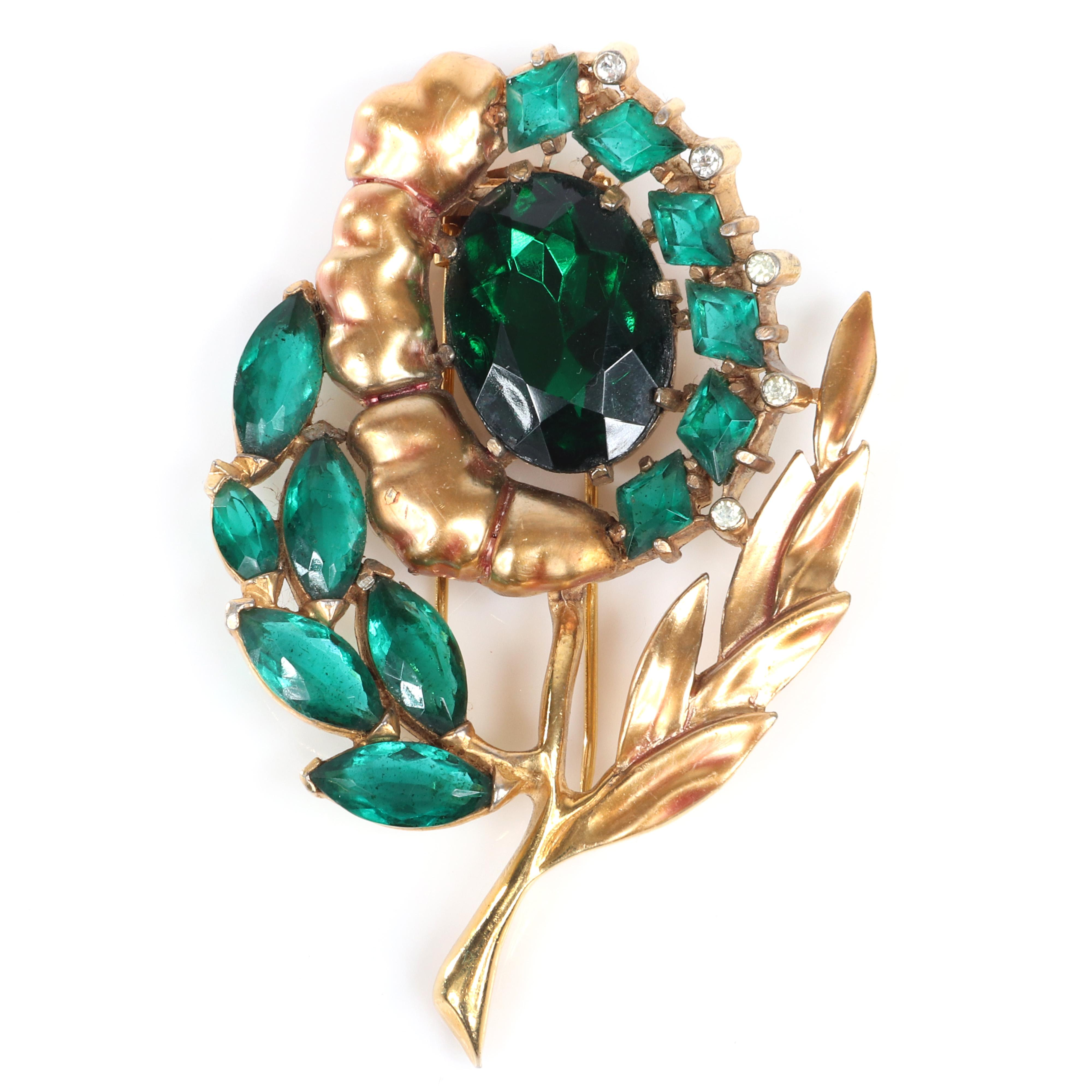 "Eisenberg Original flower fur clip with gold plating over pot metal, emerald rhinestones in marquise and diamond cut, clear bezel-sets accents and large oval central stone, 1940s. 3 3/8"" x 2 1/8"""