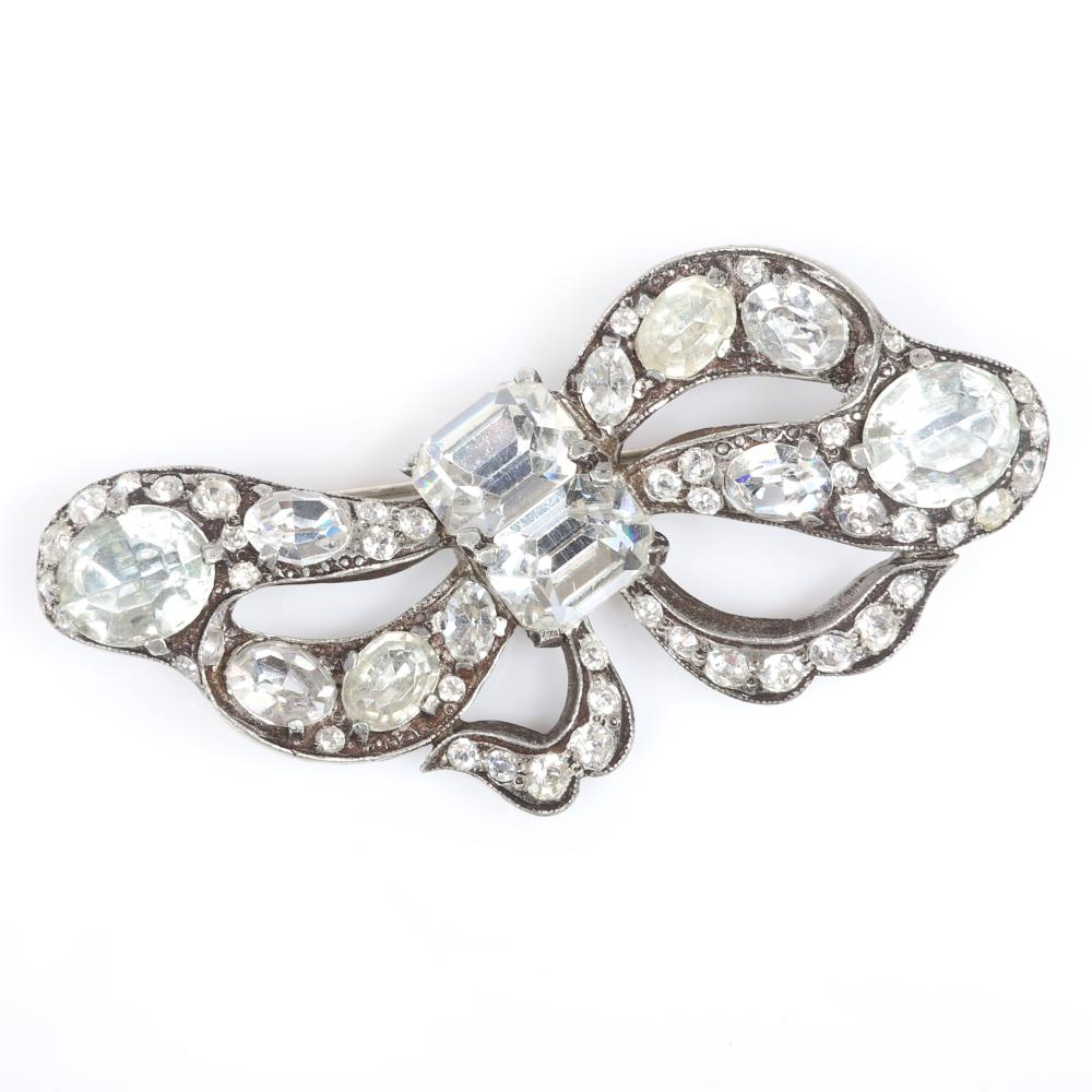 """Eisenberg Original asymmetrical bow brooch with silver pot metal, two large emerald-cut stones form the central knot and oval colorless crystals in various sizes, c. 1940. 1 3/4"""" x 3"""""""