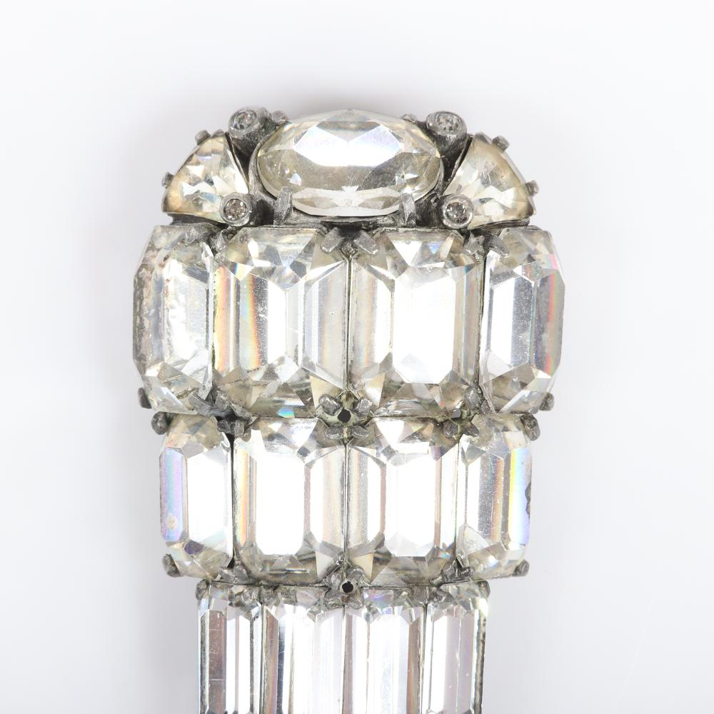 """Eisenberg Original dimensional deco dress clip with silver pot metal, top row of oval and pear stones with clear bezel accents and two rows of emerald-cut stones, early 1940s. 3 1/4"""" x 1 3/4"""""""