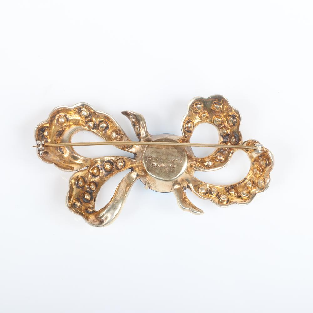 """Eisenberg Original gold washed stardust bow brooch with scalloped edge, 1"""" faceted aqua stone and incised stars with central clear rhinestone, late 1930s. 2"""" x 3 3/4"""""""