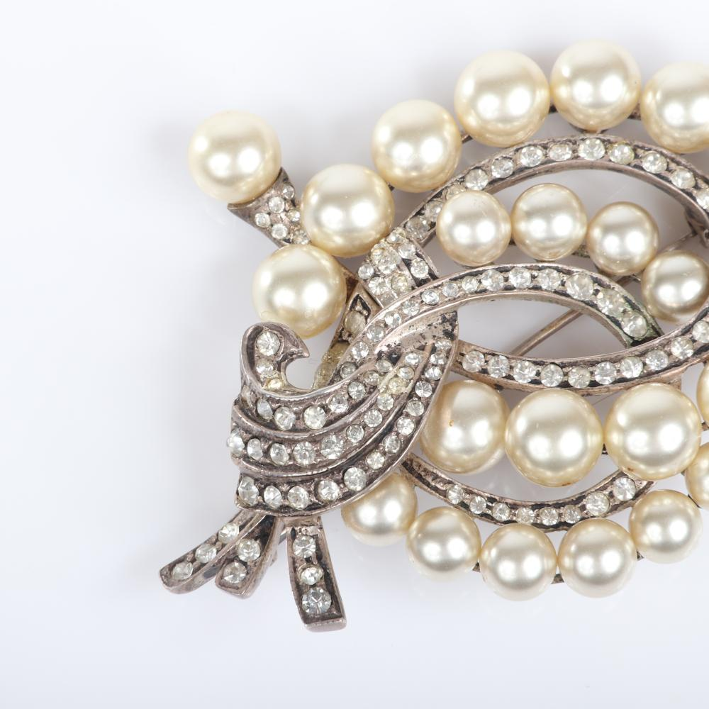 """Eisenberg Original pearl and rhinestone sterling brooch with graduated, faux white pearls swirling in loops with pave ribbons, mid-1940s. 3"""" x 3"""""""