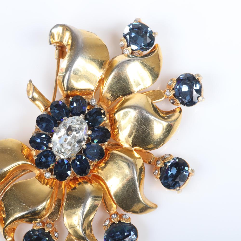 "Eisenberg Original ""Golden King's Ransom"" floral Fur Clip with gold pot metal and large clear center stone surrounded by sapphire blue crystals, appeared in ads in 1941. 3 7/8"" x 3 1/2"""