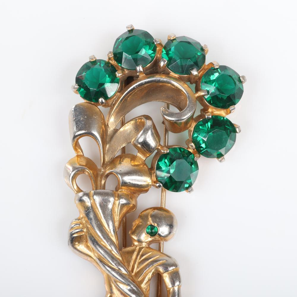 """Eisenberg Original gold plated Egyptian male figure with a green rhinestone earring holding a cornucopia with large emerald crystal flowers, c. 1940. 4"""" x 1 3/4"""""""