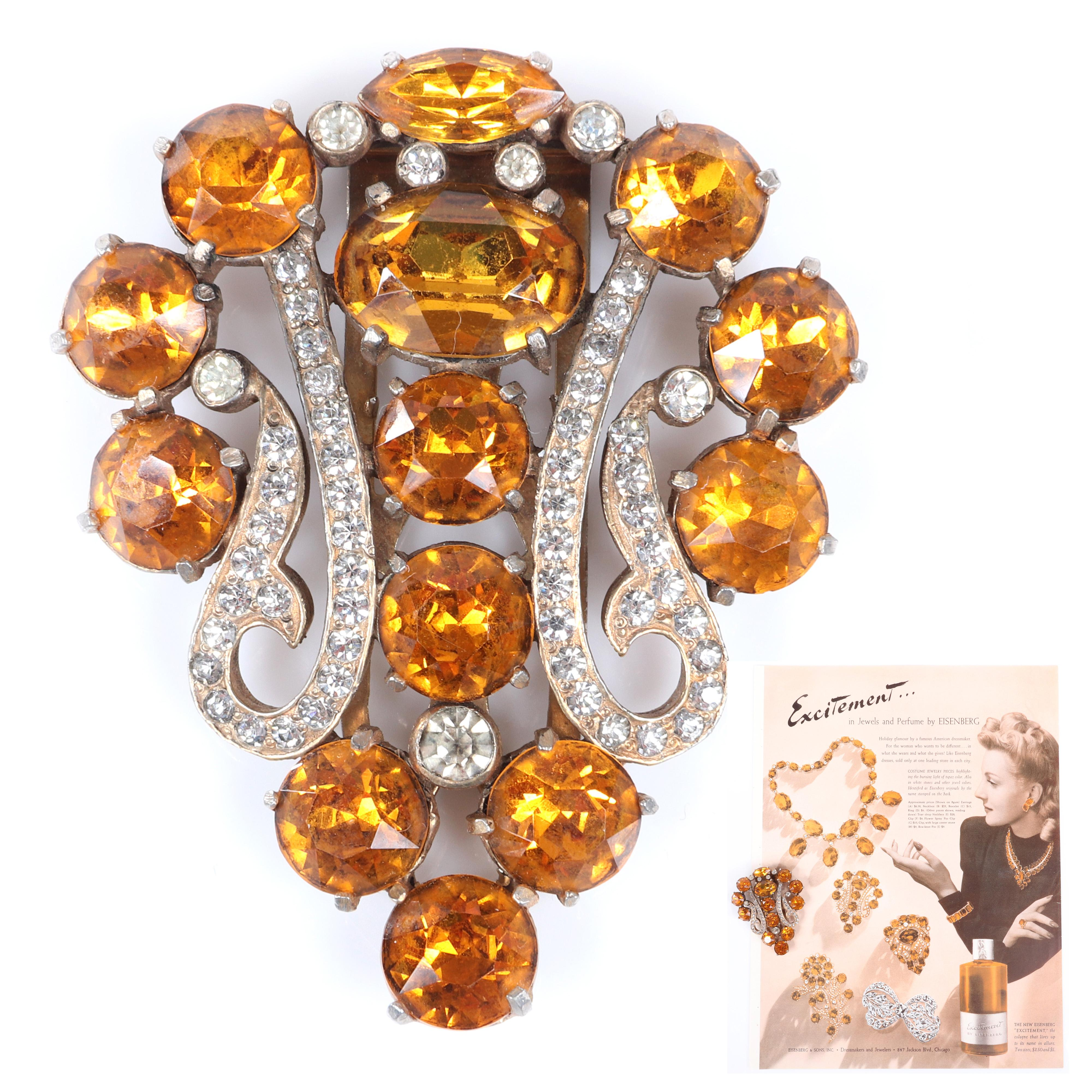 """Eisenberg Original topaz crystal shield fur clip with gold washed pot metal, large round topaz faceted crystals and bezel set rhinestones. Includes original 1940 Vogue advertisement featuring brooch. 2 3/4"""" x 2 1/4"""""""