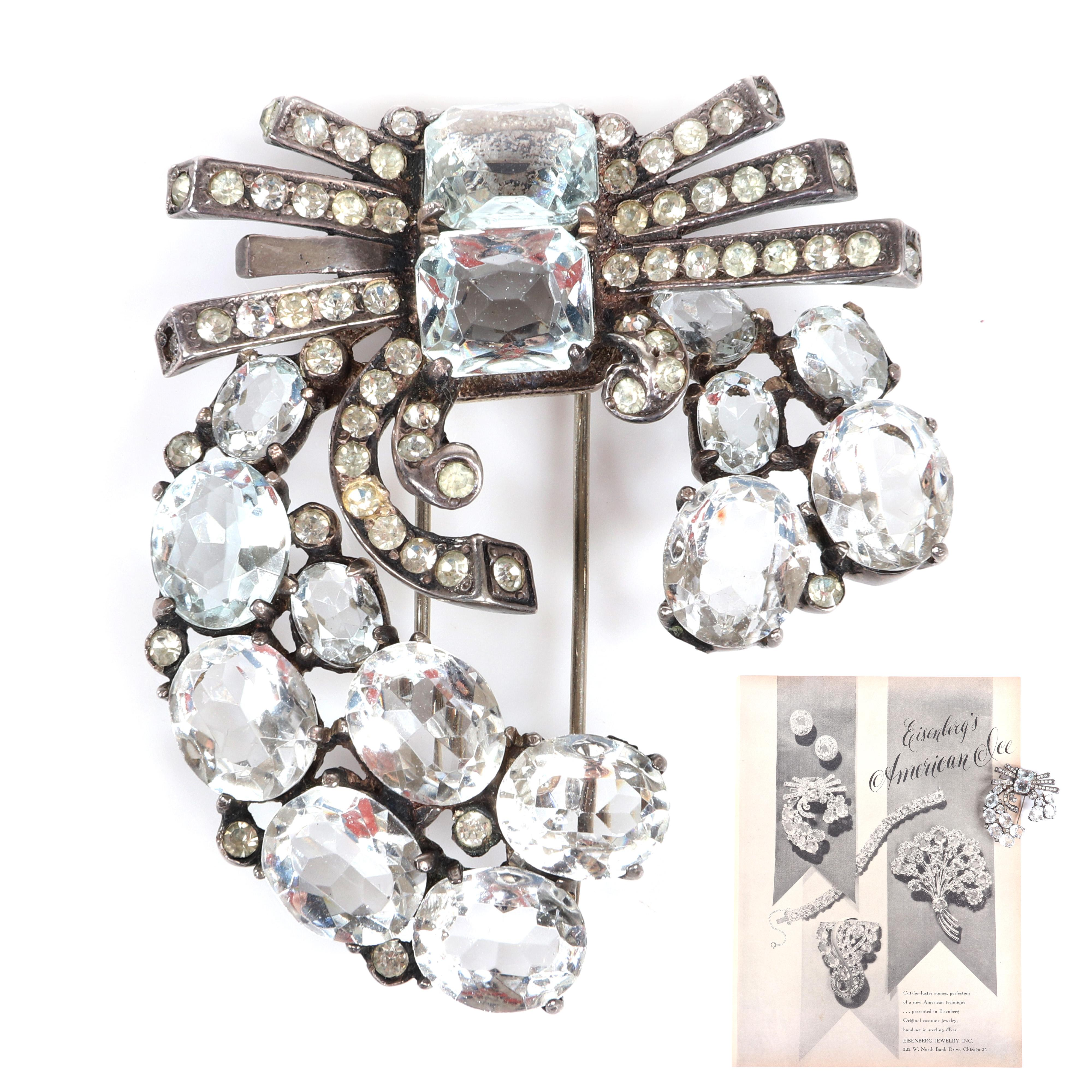 "Eisenberg Original diamante sterling fur clip with icy blue accents with large open-backed clear crystals and pave. Includes Vogue 1946 RARE advertisement featuring pin. 3 1/4"" x 2 1/4"""