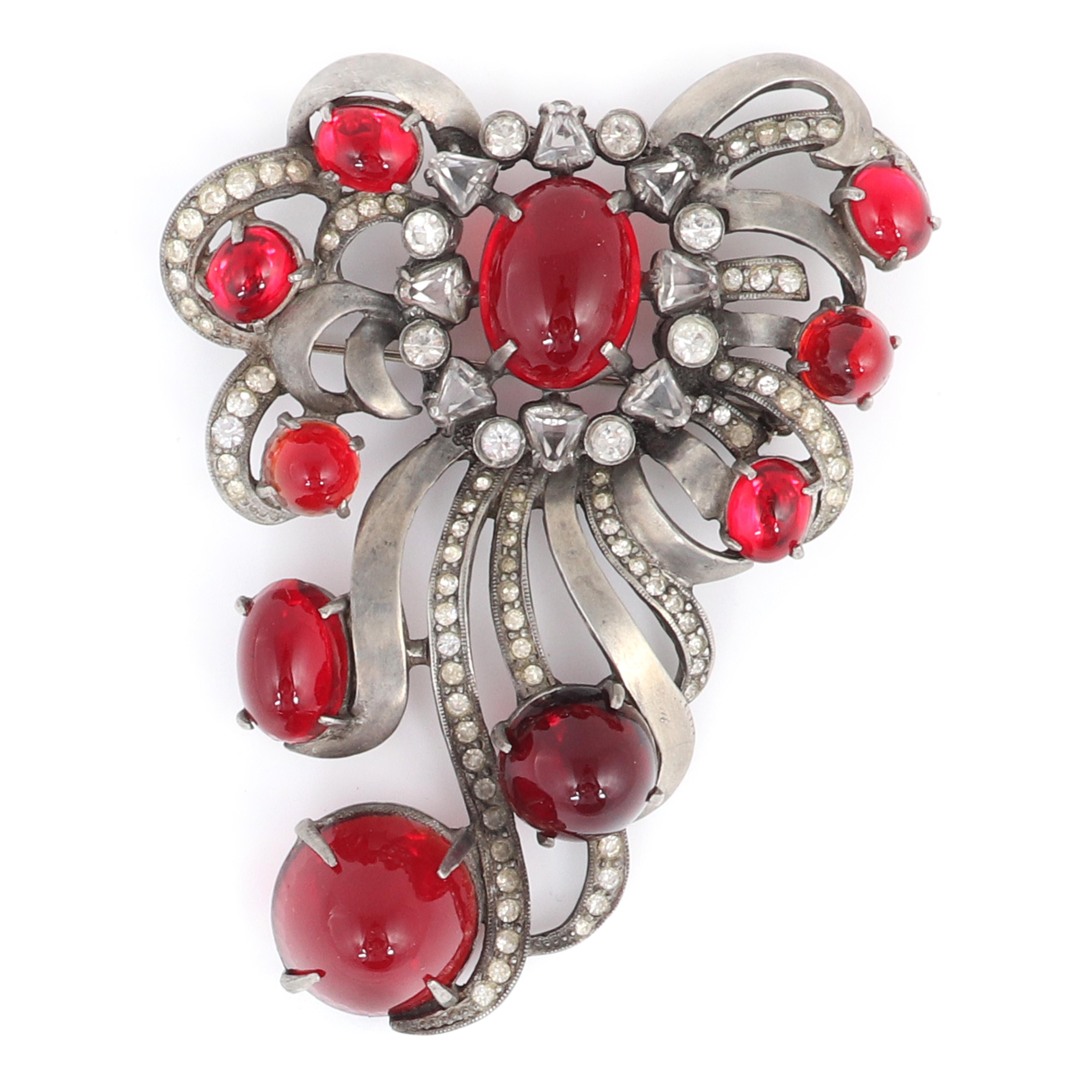 "Eisenberg Original large ruby glass cabochon brooch with silver pot metal ribbons lined with small rhinestones, bezel-set and triangular stones, late-1930s. 4"" x 3"""