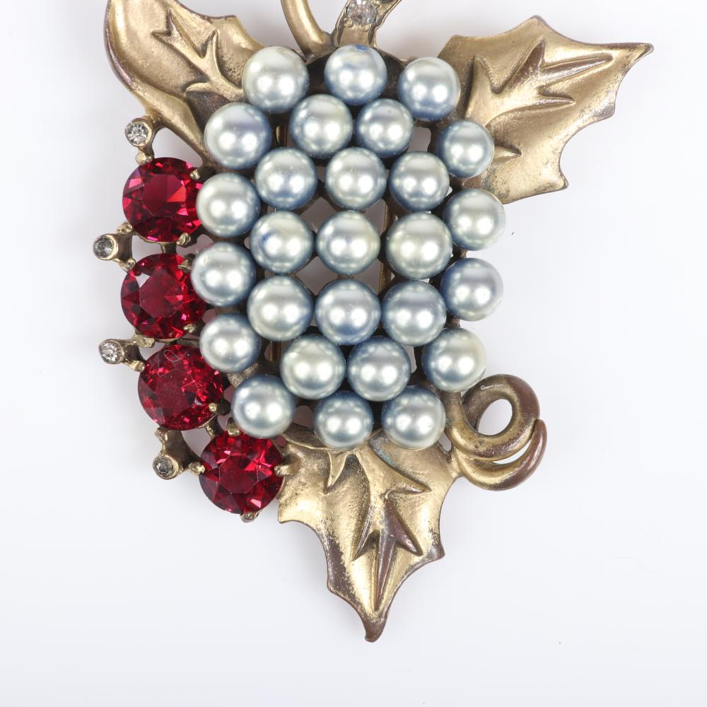 "Eisenberg Original faux grape cluster fur clip with gold washed pot metal, silver faux pearls, accented by four large unfoiled ruby crystals and bezel-set rhinestones, c. 1940. 3"" x 2 1/4"""