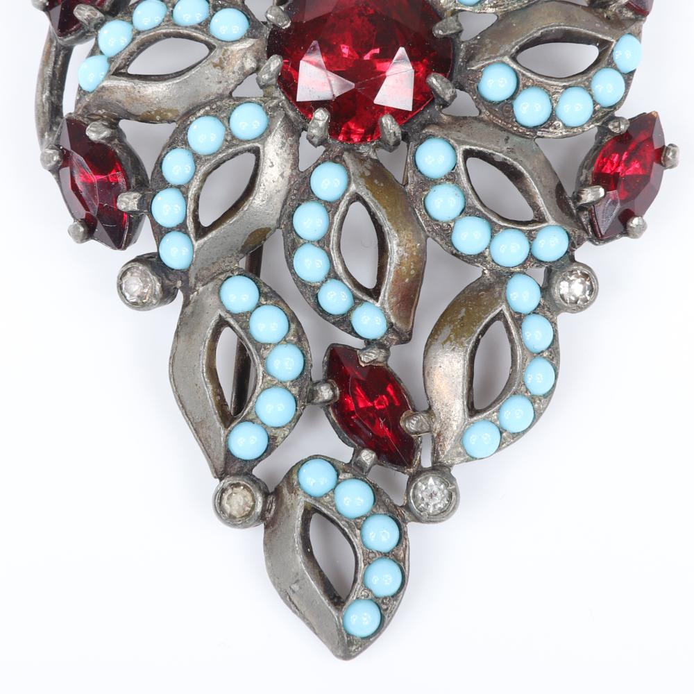 "Eisenberg Original early dress clip with antiqued gold pot metal accented with faux turquoise beads and red faceted crystals and central pinwheel, c. 1930. 2 1/2"" x 1 3/4"""