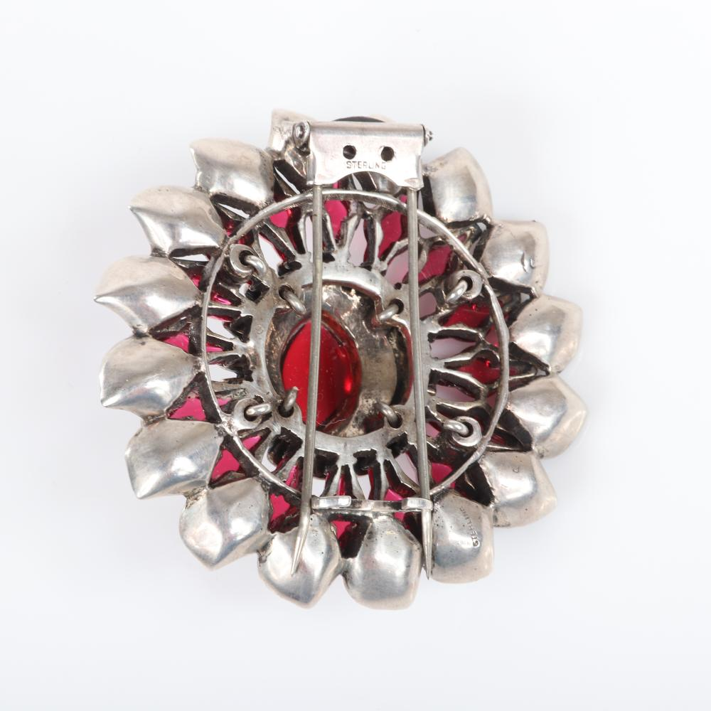 Eisenberg Original sterling layered floral fur clip with large central ruby glass cabochon, surrounded by unique glass beads, rhinestones and faux turquoise beads, c. 1945. Includes original advertisement highlighting...