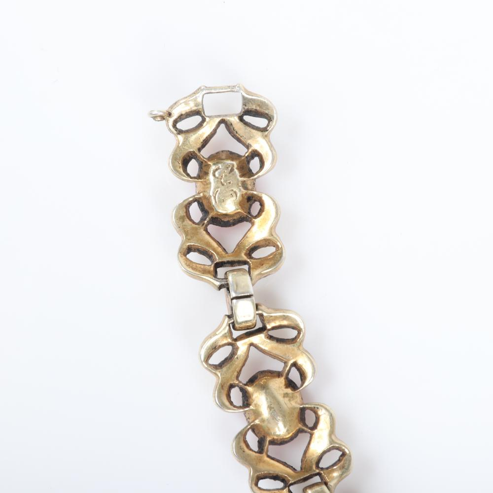 """Eisenberg Original sterling and pink crystal bracelet in six segments with elaborate gold links and central oval faceted pink stone surrounded by rhinestones, c. 1946. 7 1/4""""L x 1/2""""W"""