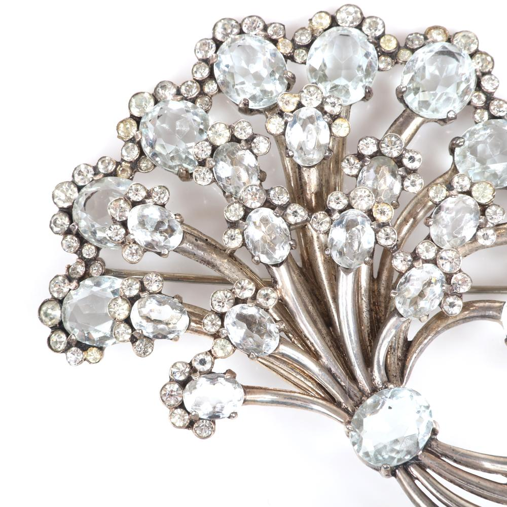 "Eisenberg Original sterling icy blue bouquet fur clip with large open-backed pale blue crystal stones with bezel-set rhinestones surrounding each flower, advertised in 1945. 3 1/2"" x 3"""