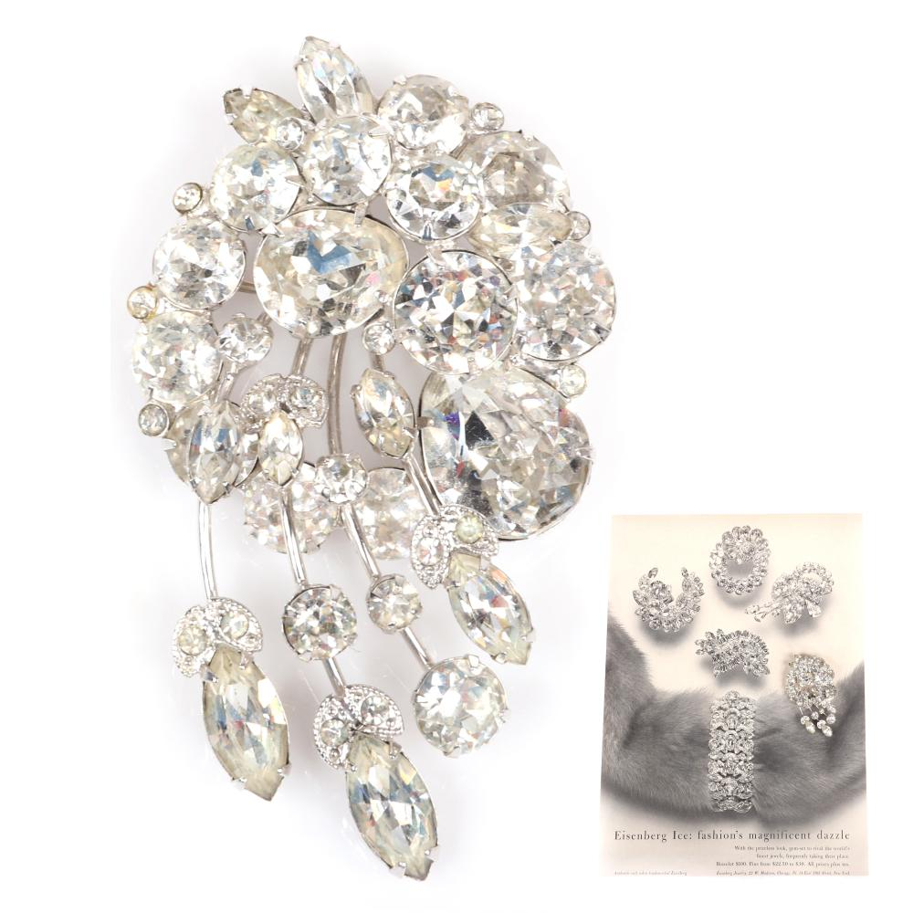 "Eisenberg cascading floral brooch in rhodium with round & marquise crystals and bezel-set rhinestones, marked Block E, 1950s, with original advertising showcasing similar pieces. 3 1/4"" x 1 3/4"""