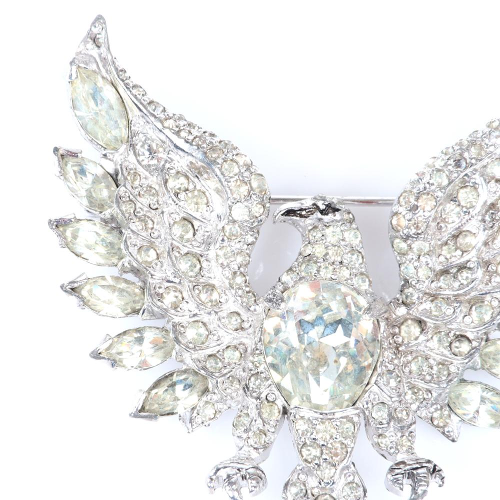 """Eisenberg Original eagle brooch in rhodium with large faceted crystal belly, pave and marquise crystal feathers, page 156, figure 6.25. Includes 1950s Bergdorf Goodman advertising. 2 1/4"""" x 2 1/4"""""""