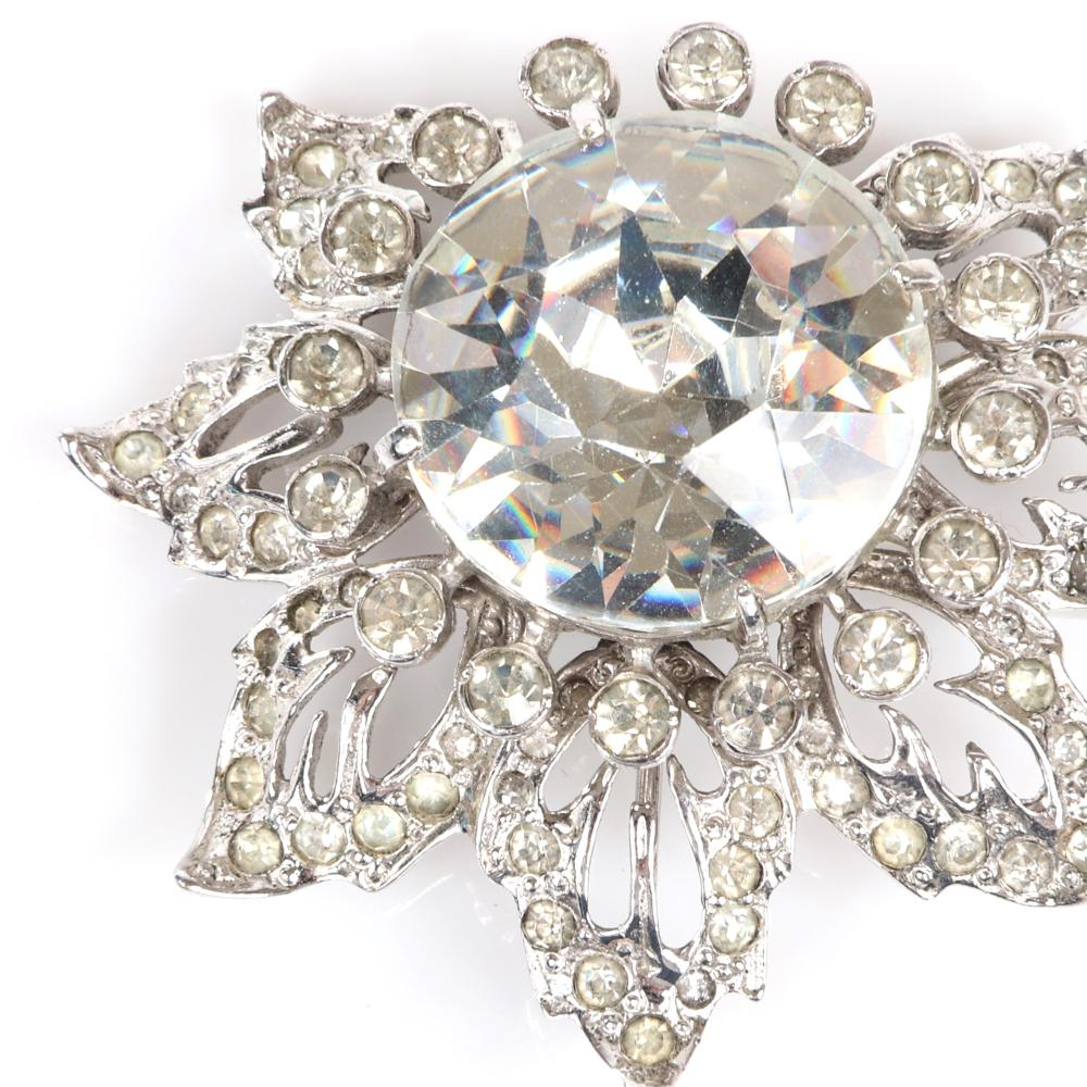 """Eisenberg Original sterling floral brooch with large central rhinestone surrounded by bezel-set stones layered over open work pave leaves, mid 1940s. 1 3/4"""" x 2"""" (brooch), 1"""" diam. (central crystal)"""