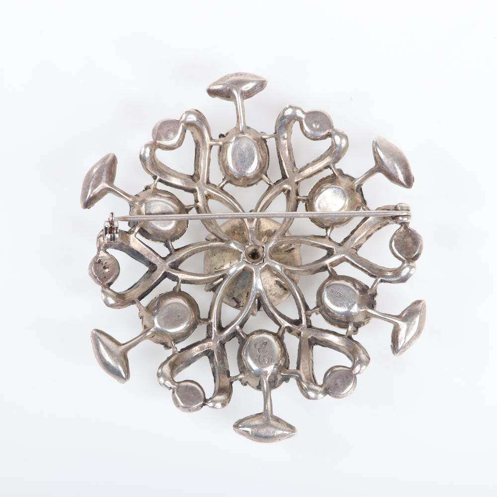 "Eisenberg Original sterling dimensional openwork snowflake brooch with ribbon loops of pave and bezel-set stones, marked script E, mid-1940s. Includes original 1945 advertising. 3"" diam"