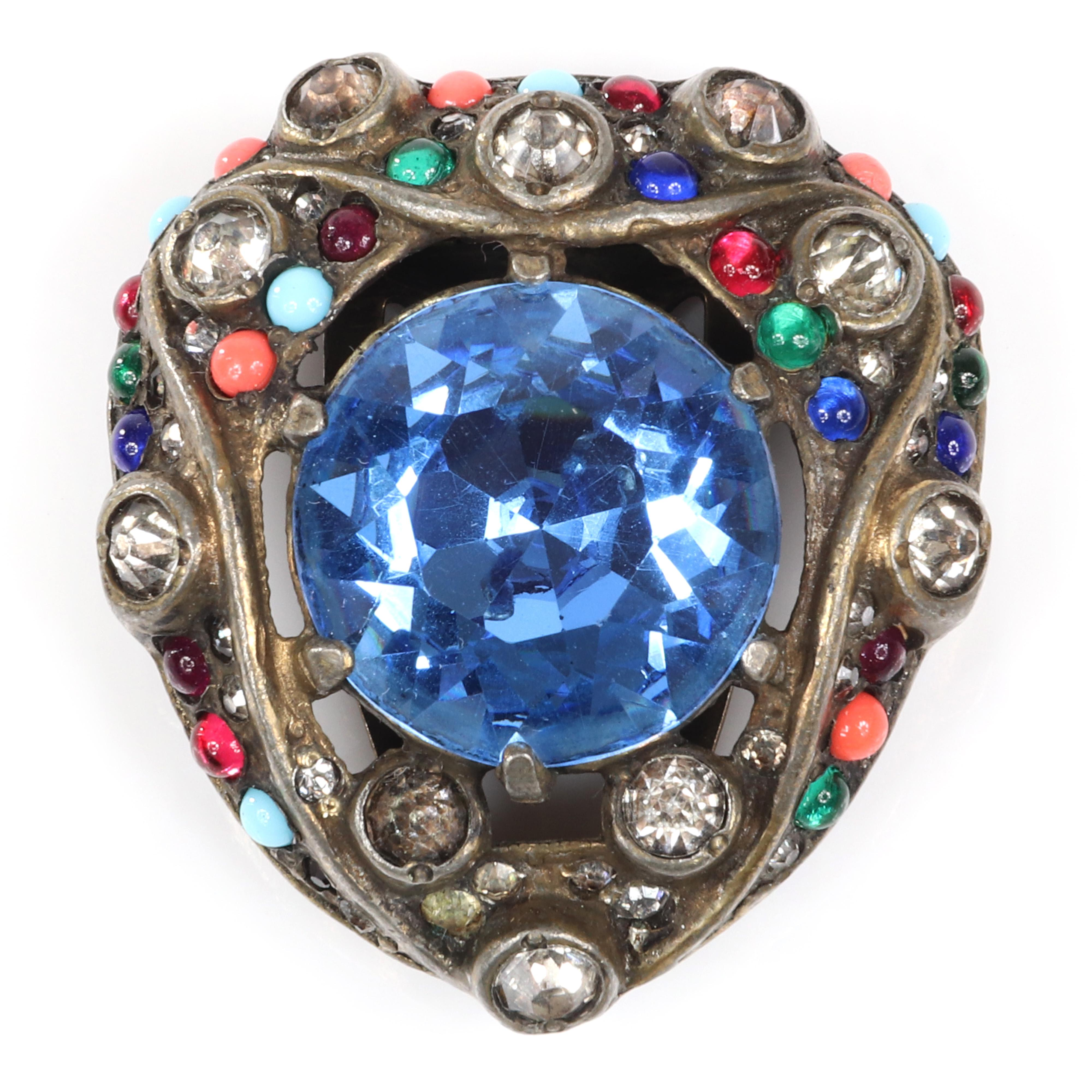 """Eisenberg Original striking dress clip with antiqued silver pot metal, a large central blue open backed crystal, bezel-set rhinestones and multi-colored glass beads, c. 1930s. 1 1/2"""" x 1 3/4"""""""