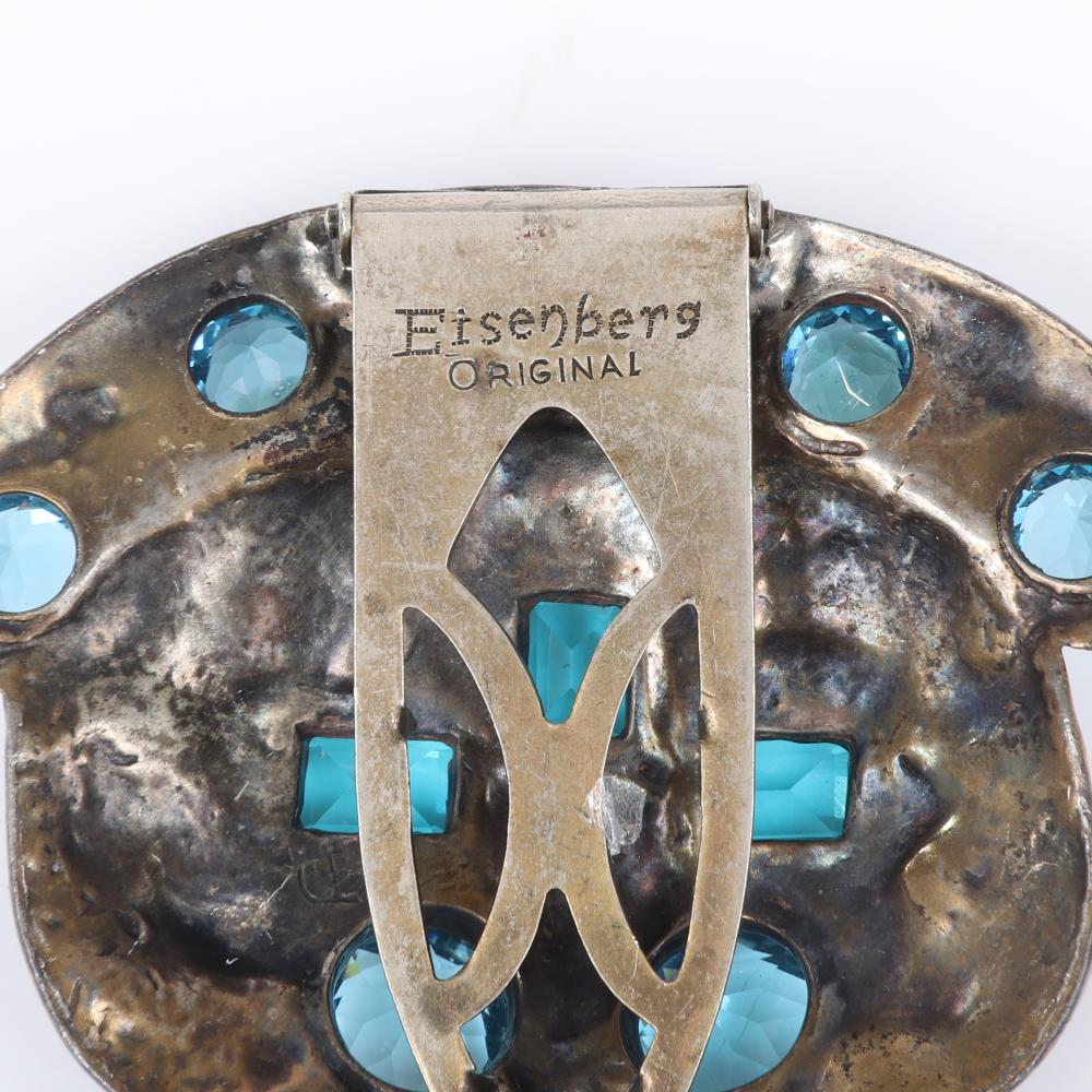 """Eisenberg Original antiqued gold pot metal shield fur clip with 7 pale blue large round crystals, 3 turquoise emerald-cut stones with multi-colored cabochons, late 1930s. 2 1/4"""" x 2 1/4"""""""