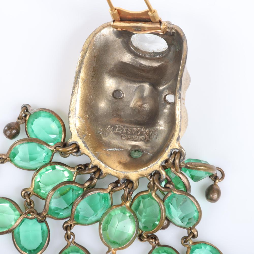 "Eisenberg Original gold plated Asian Mask fur clip with dimensional face with pave and crystal top and dangling fringe lines of 18 emerald open-backed rhinestones, c. 1940. 4 1/2"" x 2"""