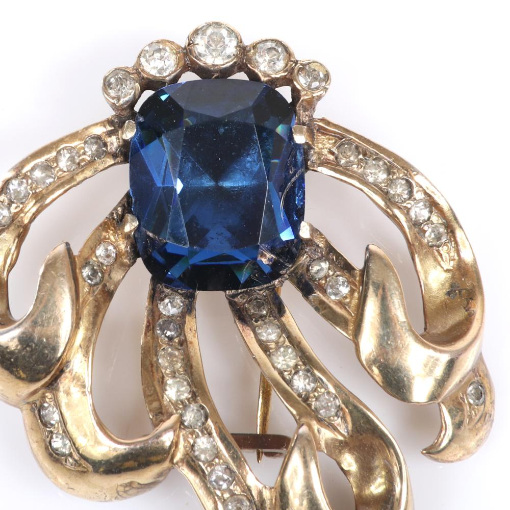 "Eisenberg Original sterling vermeil fur clip with large central blue faceted crystal rimmed with bezel-set rhinestones and curling pave lined ribbons, mid-1940s. 2 1/4"" x 2"""