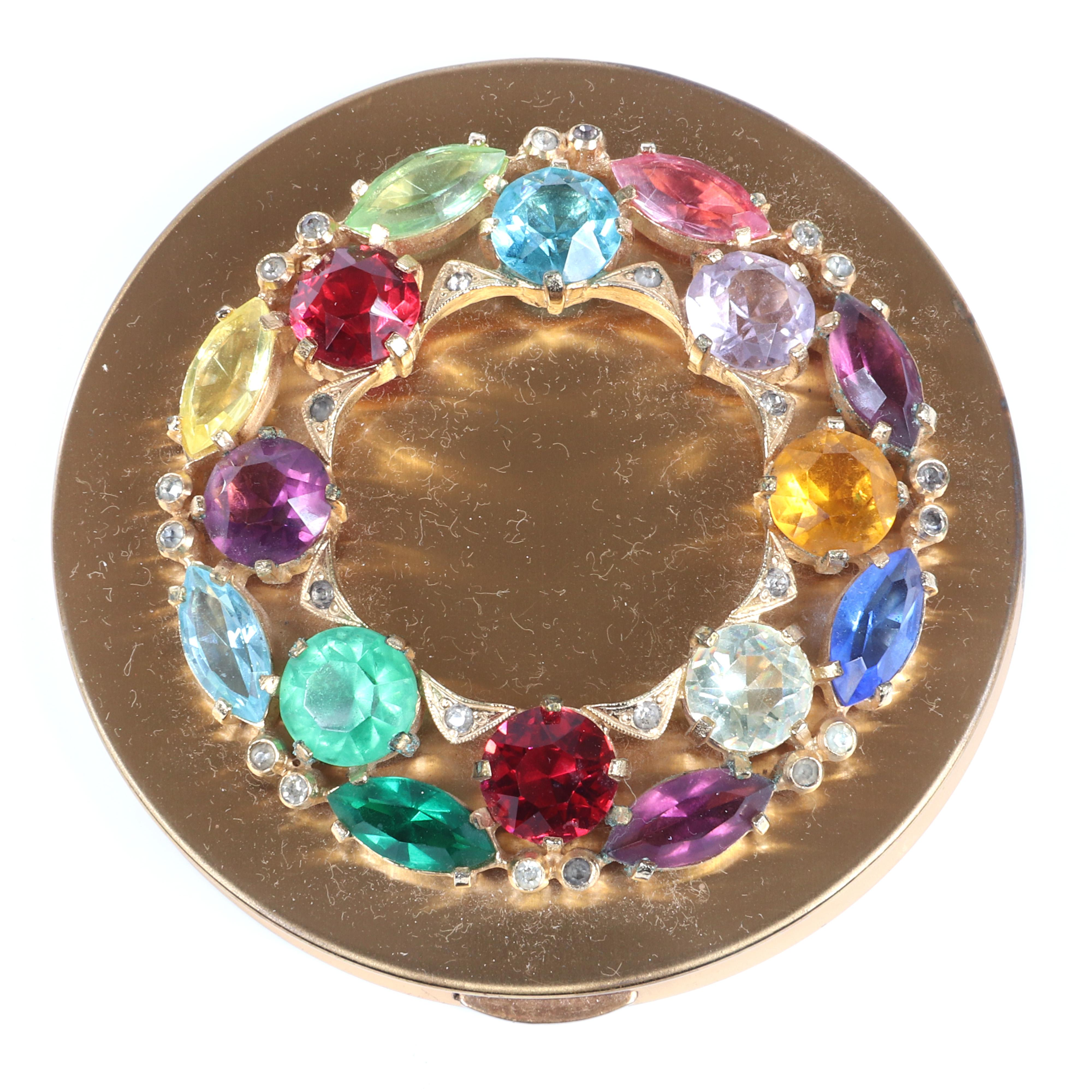 """Eisenberg Original colorful round compact with powder & puff and inner band of gold triangles with bezel-set clears, two rows of multi-color round & marquise stones, c. 1940s. 3 1/2"""" diam."""