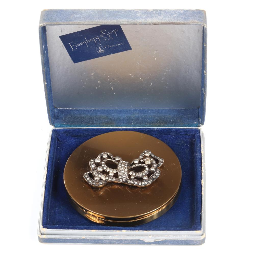 """Eisenberg Original round gold tone compact with rhinestone bow with silver pot-metal ribbon bow with scalloped edges in bezel and pave-set stones in original box, c. 1940s. 3 1/2"""" diam."""