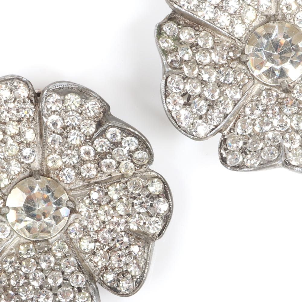 "Eisenberg Original pair of early flower diamante dress clips in silver pot metal with large central rhinestone surrounded by pave petals, c. 1930s. 1 3/4"" diam. (each)"